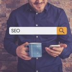 Man holding cell phone with the words SEO typed into a search bar